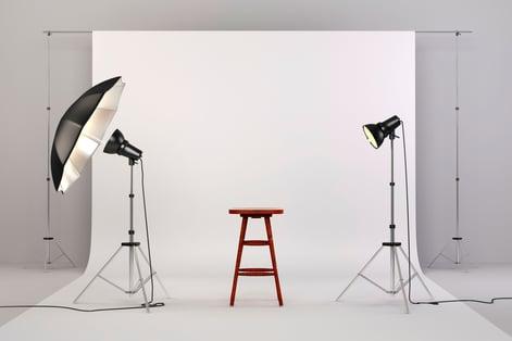 Studio med en brun krakk og lamper for å sikre riktig lyssetting før video spilles inn.